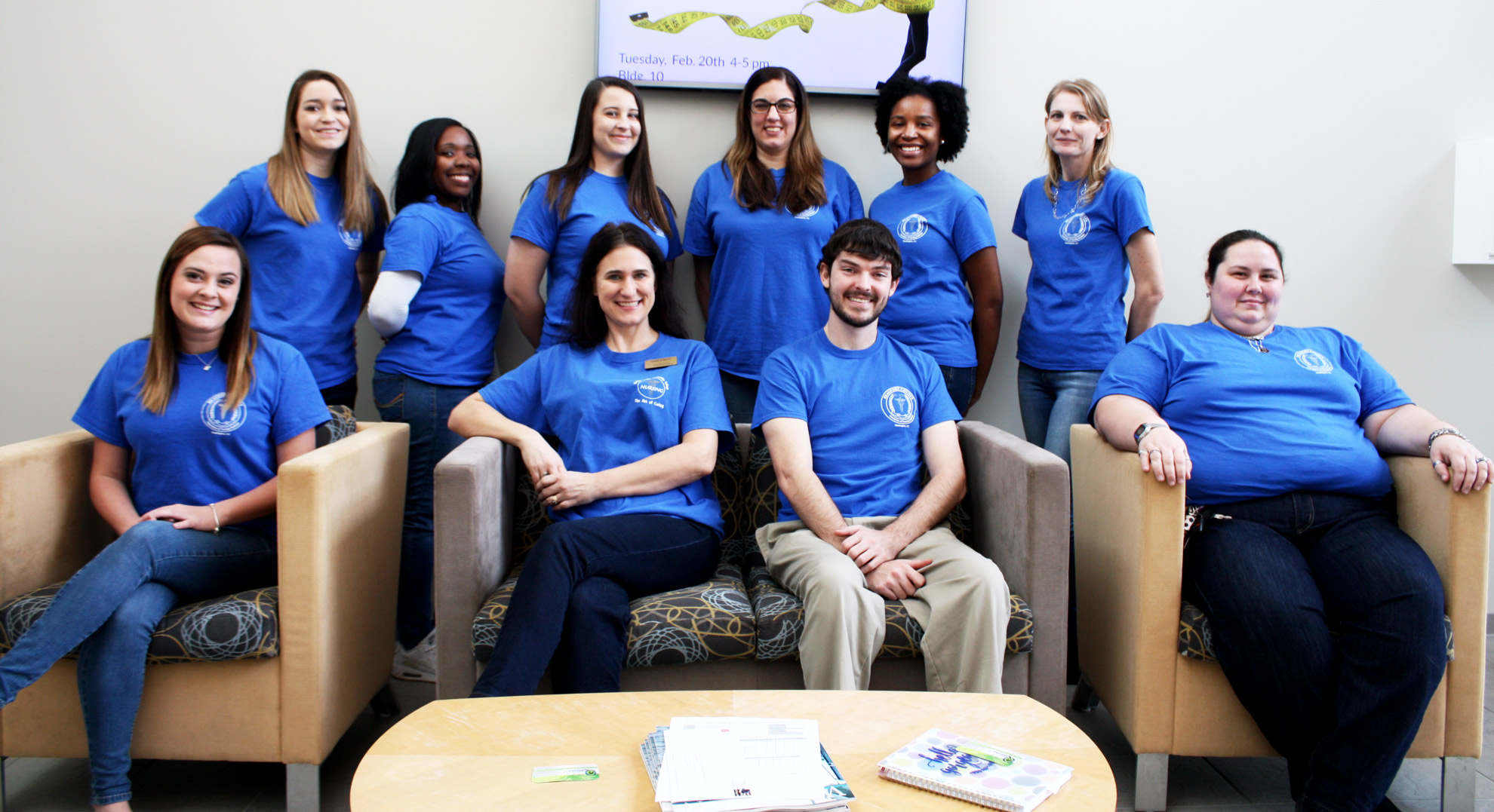 Ten students in blue t-shirts in two rows. Front row (left to right): Makayla Cutler, VP; Angela Boyd, Faculty Advisor; James Matthews, President; and Jessie Godley, Social Event Coordinator. Back row (left to right): Logan Barber, Historian; India Allen, LPN Rep; Brittany Wiggins, Historian; Kristen Battershell, Secretary; Michelle Ashe, Treasurer; and Daniell Davenport, Social Event Coordinator.  Not pictured: Morgan Peed, LPN representative.