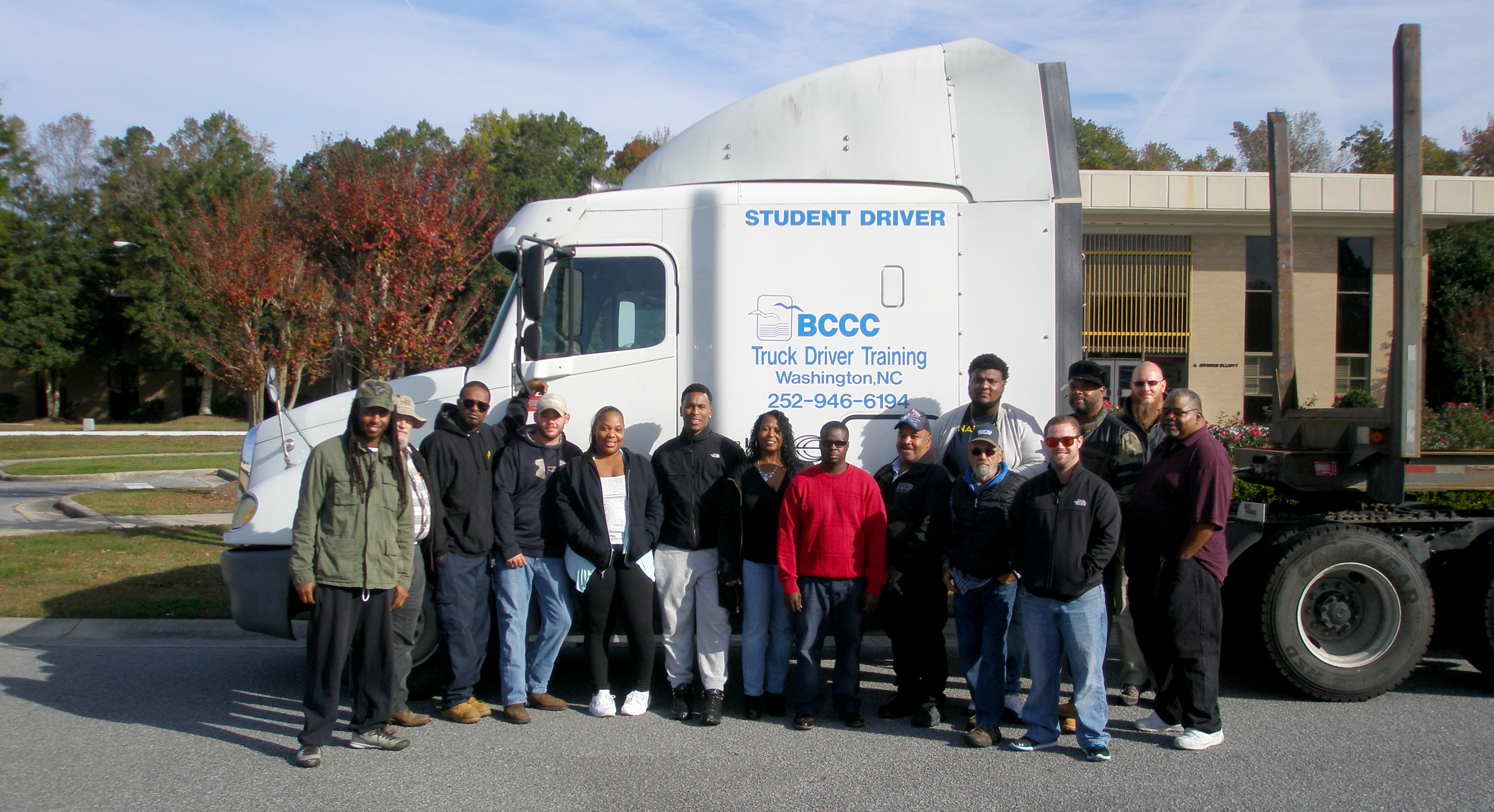 A dozen students stand in front of a truck cab in front of the college.