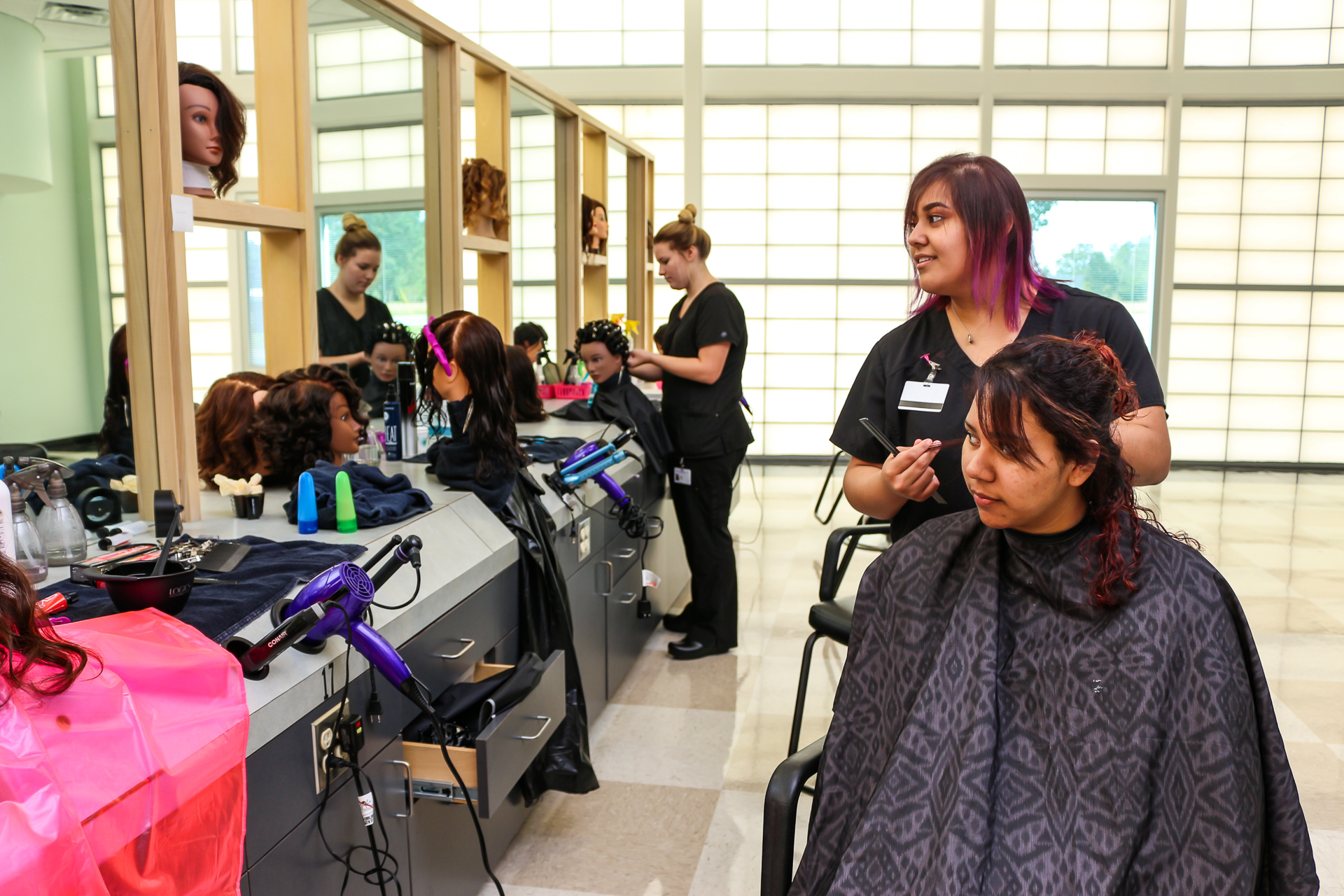 A student cutting hair in the cosmetology salon.