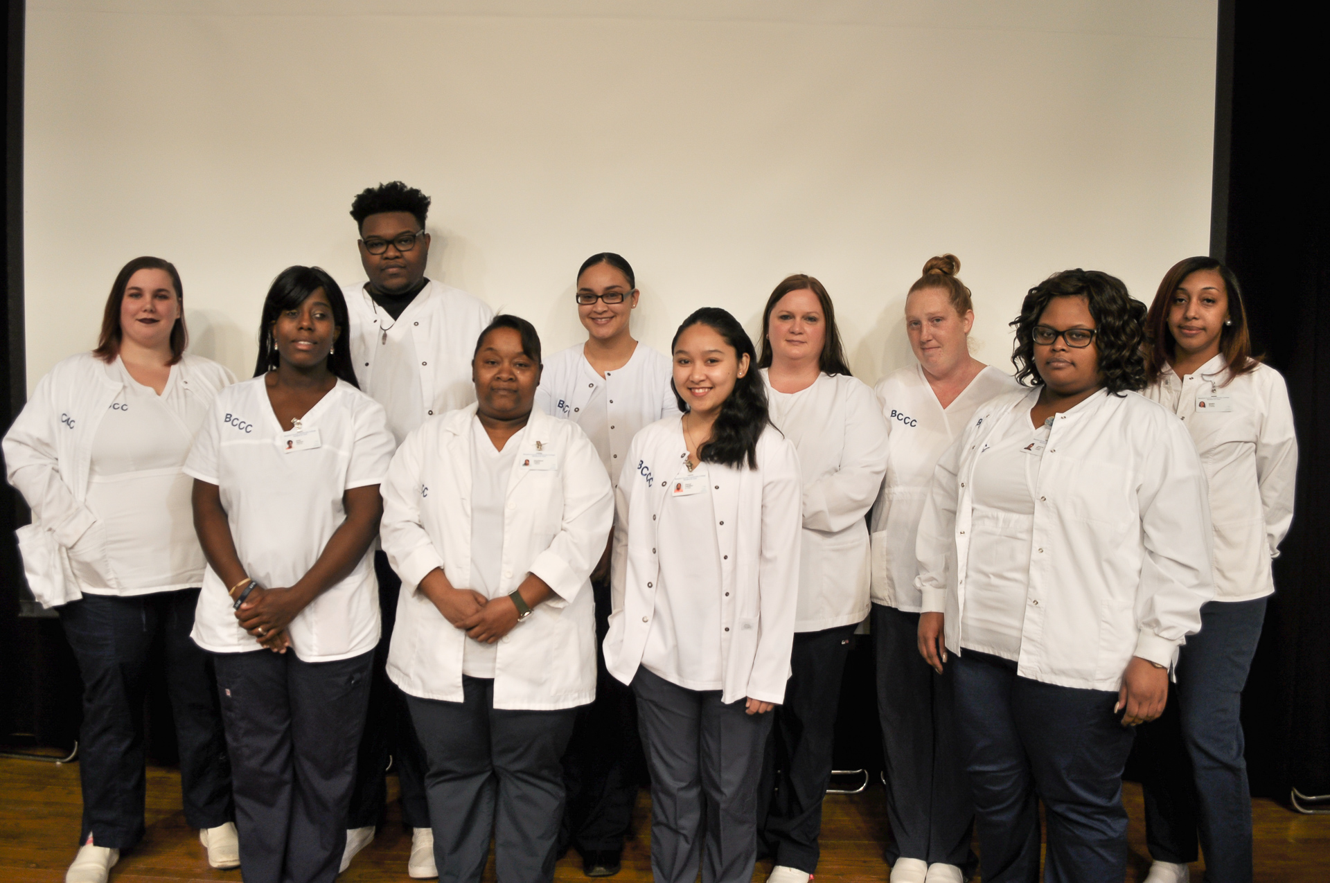 About a dozen students in white coats posing against a white background.