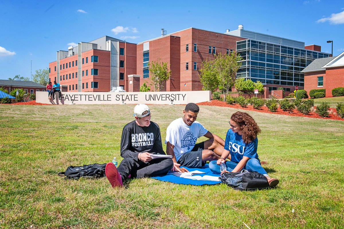 Three students in front of a sign that reads Fayetteville State University.